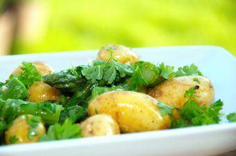 En nem kartoffelsalat med friske grønne asparges, persille og en let og syrlig dressing. Den kolde kartoffelsalat er den perfekte sommersalat til mad fra grillen, og så kan den laves noget tid i forvejen. Foto: Madensverden.dk.