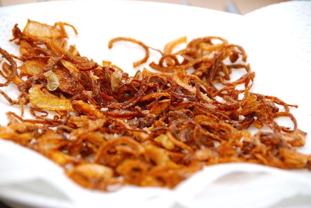 De ristede løg lægges til afdrypning på et stykke køkkenrulle, fordi det tager det værste af fedtindholdet. Løgene indeholder dog fortsat en hel del kalorier. Foto: Madensverden.dk.