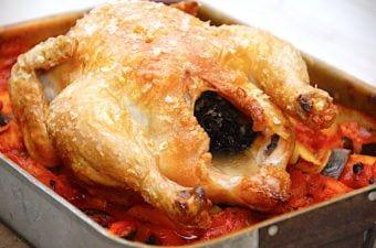 billede med hel kylling i ovn på bund af rodfrugter