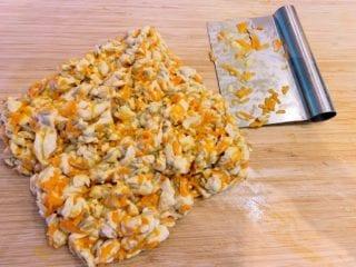 Dejen til dine gulerodsbrud hakkes nu godt ud. Brug gerne en metalskraber, men en kniv kan også bruges. Saml dejen efterhånden som æggene løber ud. Foto: Holger Rørby Madsen, Madensverden.dk.