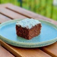 Denne kakaokage er super god til at have med på tur eller som klassens time kage. Her er den med hvid glasur og kokos, men du kan pynte den, som du vil. Foto: Charlotte Mithril