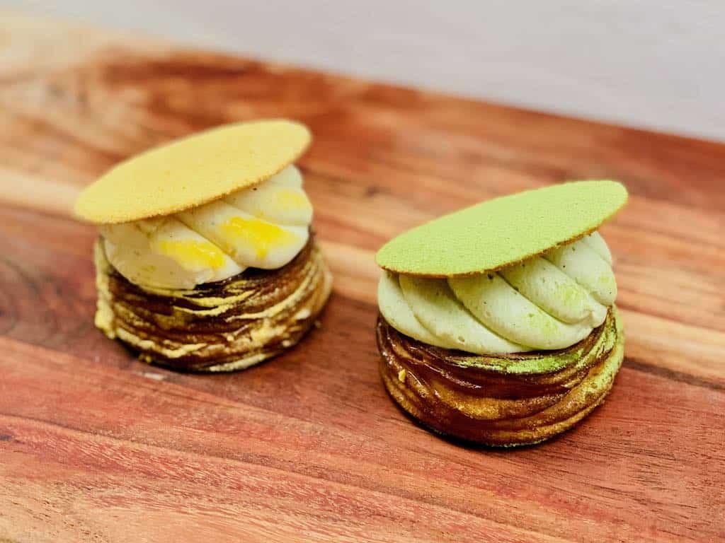 Det er luksus fastelavnsboller som disse fra Andersen Bakery til 48 kroner stykket, som folk står i kø for. Her er det æble-yuzu til venstre og hindbær-matcha til højre. Foto: Charlotte Mithril