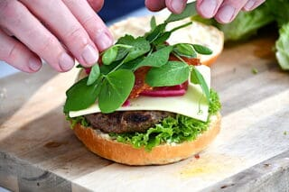 verdens bedste burger toppes med friske ærteskud