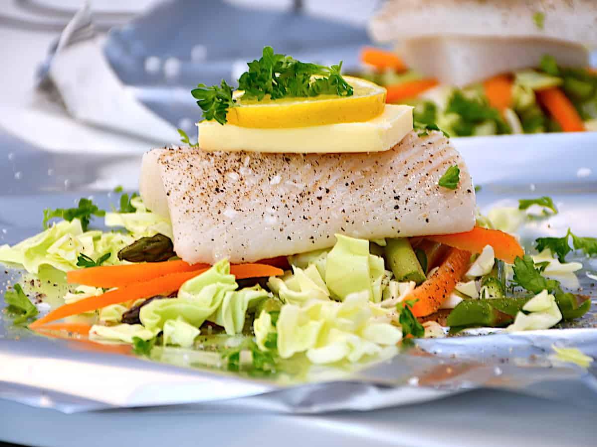 Grillet hellefisk i staniol med grøntsager er en lækker måde at tilberede hellefisken på. Her lavet i pakke med bla. spidskål og gulerødder, og pakkerne kan enten tilberedes i grill eller ovn. Foto: Holger Rørby Madsen, Madensverden.dk.