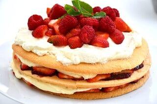 den færdige sommerlagkage med jordbær og hindbær på toppen
