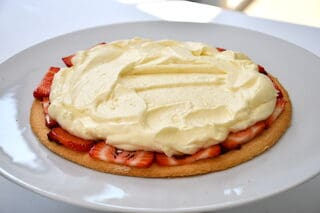 fordel flødecreme på jordbærrene til din lagkage