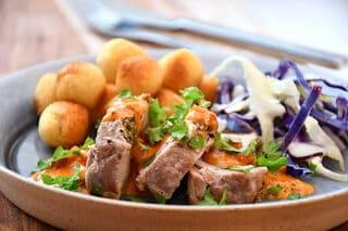 hasselback svinemørbrad serveret med spidskålssalat og kartofler samt baconsovs